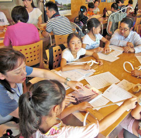紐の結び方を教わる子供たち