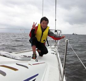 ヨットの先端でピースをする子ども